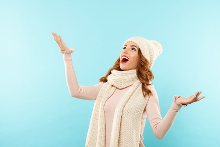 Portrait of a happy cheerful girl dressed in winter clothes catching snowflakes isolated over blue background Stock Photo