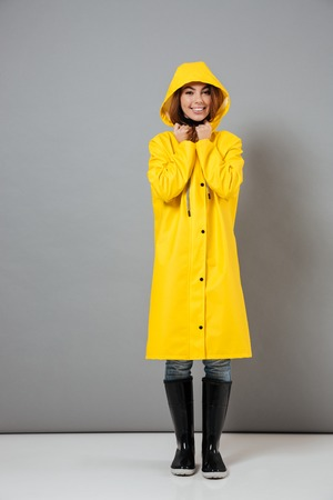 Full length portrait of a smiling girl dressed in raincoat and rubber boots posing with hood on her head and looking at camera isolated over gray background Stock Photo - 93622916