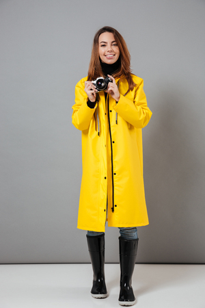 Full length portrait of a happy girl dressed in raincoat standing and holding retro camera isolated over gray background