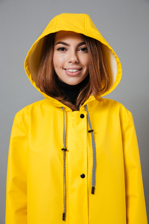 Portrait of a cheerful girl dressed in raincoat posing with hood on her head and looking at camera isolated over gray background Stockfoto