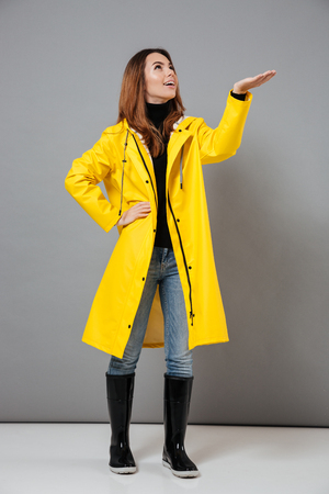 Full length portrait of an attractive girl dressed in raincoat and rubber boots posing while standing isolated over gray background