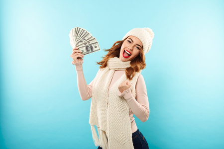 Portrait of a joyful pretty girl dressed in hat and scarf holding bunch of money banknotes and looking at camera isolated over blue background
