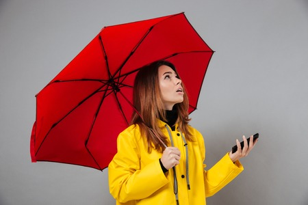 Portrait of a pretty girl dressed in raincoat looking up at copy space while standing with an open umbrella and holding mobile phone isolated over gray background