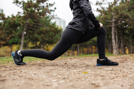 Cropped image of a fitness girl stretching legs outdoors