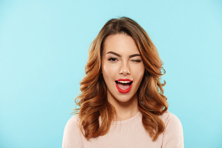 Close up portrait of a cheerful young girl dressed in sweater looking at camera and winking isolated over blue background