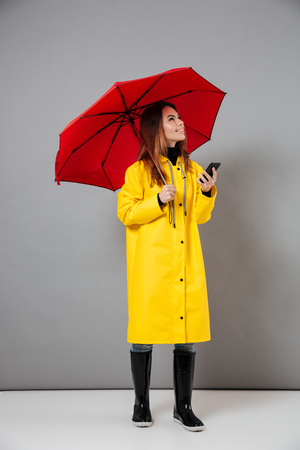 Full length portrait of a smiling girl dressed in raincoat and rubber boots posing while standing with an open umbrella and holding mobile phone isolated over gray background