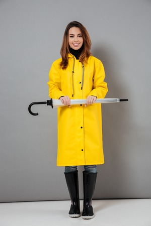 Full length portrait of a smiling girl dressed in raincoat and rubber boots posing while standing with an umbrella isolated over gray background Foto de archivo