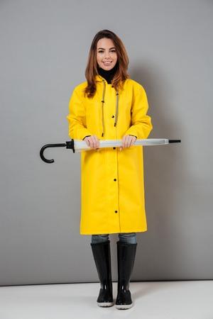 Het volledige lengteportret van een glimlachend meisje kleedde zich in regenjas en rubberlaarzen die terwijl status met een paraplu stellen die over grijze achtergrond wordt geïsoleerd Stockfoto