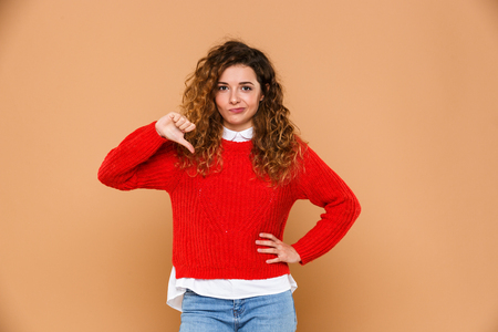 Portrait of an upset disappointed girl standing and showing thumbs down gesture isolated over beige background