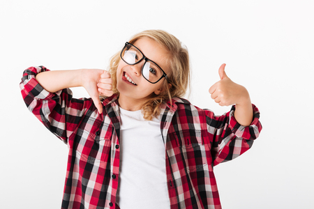Portrait of a joyful little girl in eyeglasses showing thumbs up and thumbs down isolated over white background