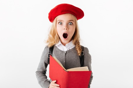 Portrait of a shocked little schoolgirl dressed in uniform holding book and looking at camera isolated over white background Stock Photo