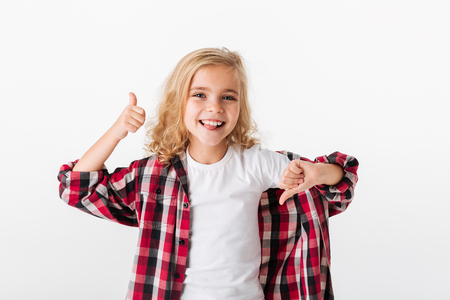 Portrait of a smiling little girl in eyeglasses showing thumbs up and thumbs down isolated over white background
