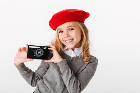 Portrait of a happy little schoolgirl dressed in uniform holding retro camera isolated over white background