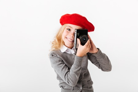 Portrait of a cute little schoolgirl dressed in uniform taking a shot with a retro camera isolated over white background Stockfoto