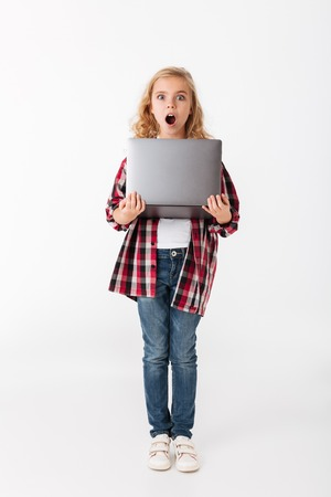Full length portrait of a shocked little girl holding laptop computer while standing and looking at camera isolated over white background Foto de archivo