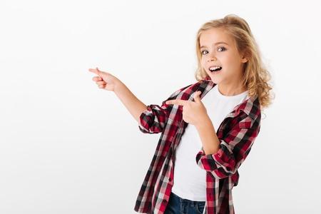 서서 흰색 배경 위에 격리 복사본 공간에서 멀리 두 손가락을 가리키는 흥분된 어린 소녀의 초상화