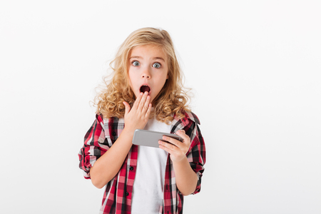 Portrait of a shocked little girl holding mobile phone and looking at camera isolated over white background Archivio Fotografico