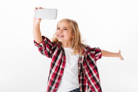 Portret van een opgewonden meisje dat een selfie neemt die over witte achtergrond wordt geïsoleerd