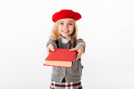 Close up portrait of a happy little schoolgirl dressed in uniform giving book and looking at camera isolated over white background