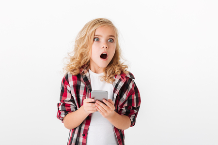 Portrait of a shocked little girl holding mobile phone and looking away isolated over white background Foto de archivo