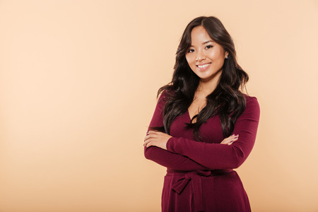 Portrait of elegant asian female in pretty maroon dress posing on camera with arms folded, isolated over peach background