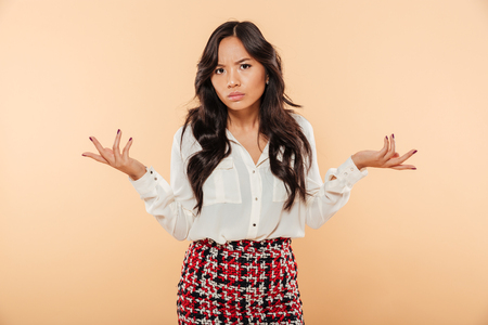 Portrait of a confused asian woman standing and shrugging shoulders isolated over beige background