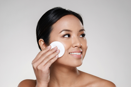Beauty portrait of a happy half asian woman removing make-up with a cotton pad and looking away at copy space isolated over gray background