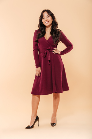 Full size portrait of charming asian female in pretty maroon dress posing over beige background, with brilliant smile and hand on waist