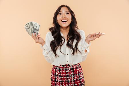Retrato de uma mulher asiática feliz segurando o monte de notas de dinheiro isoladas sobre fundo bege
