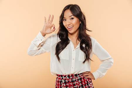 Young woman with asian appearance showing alright gesture, being happy and isolated over peach background