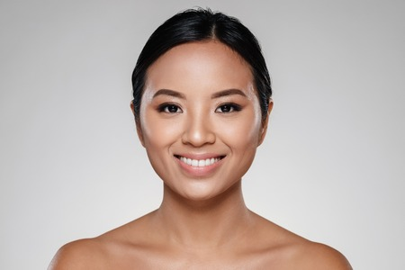 Beauty portrait of a beautiful half asian woman looking at camera isolated over gray background Foto de archivo