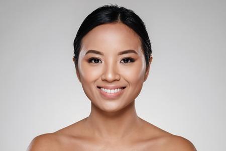 Schönheitsporträt einer schönen europäischen Asiatin , die Kamera über grauem Hintergrund lokalisiert betrachtet Standard-Bild - 93809343