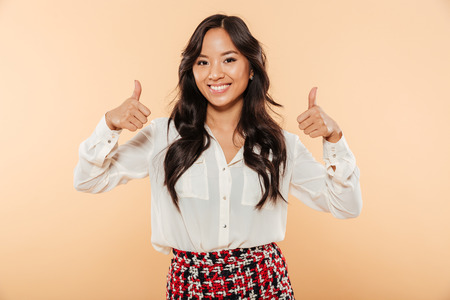 Portrait of asian candid female in casual looking at camera showing thumbs up gesturing like sign, being isolated over peach background