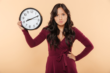Adult lady with curly long hair holding clock with time after 8 showing anger with facial expressions, putting hand on waist over beige background