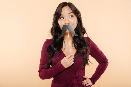 Portrait of elegant asian female in pretty maroon dress having fun on peach background, putting artificial mustaches over mouth Imagens
