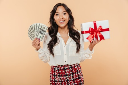 Portrait of a happy asian woman holding bunch of money banknotes and a gift box isolated over beige background