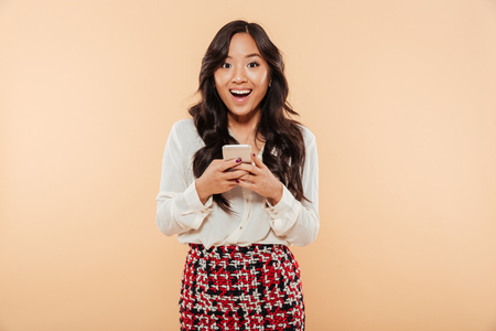 Portrait of an excited asian woman standing and using mobile phone isolated over beige background