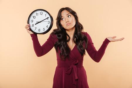 8後の時間を示す時計を保持するカール長い髪を持つ困惑ブルネットの女性は、彼女が遅れているか、桃の背景を気にしないようなジェスチャー