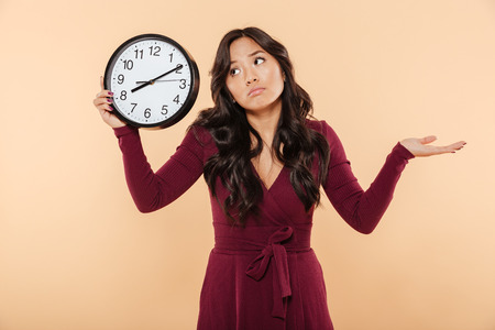 Verbaasde brunette vrouw met krullend lang haar met klok met tijd na 8, gebaren alsof ze te laat is of zich geen zorgen maakt over perzikachtergrond