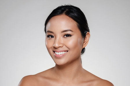 Beauty portrait of a smiling half asian woman looking at camera isolated over gray background