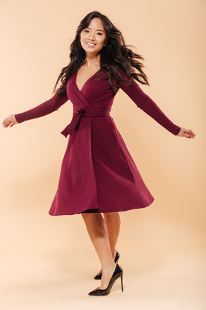 Full size portrait of charming asian female in pretty maroon dress dancing and looking on camera, being isolated over beige background