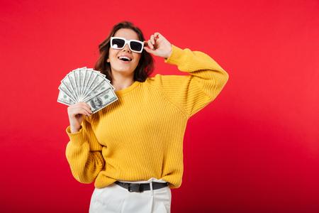 분홍색 배경 위에 절연 돈 지폐의 무리를 들고 포즈를 취하는 선글라스에 행복 한 여자의 초상화