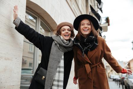 도시 거리를 걷고 가을 옷 입은 두 명랑한 여자의 초상화