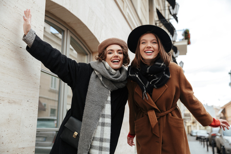 Portrait of two cheery girls dressed in autumn clothes walking on a city street Reklamní fotografie
