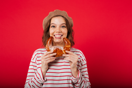 Portrait of a smiling woman wearing beret holding croissant and looking at camera isolated over pink background