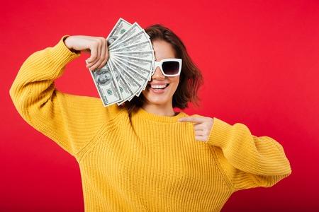 Porträt einer lächelnden Frau bei der Sonnenbrilleaufstellung beim Halten des Bündels Geldbanknoten lokalisiert über rosa Hintergrund