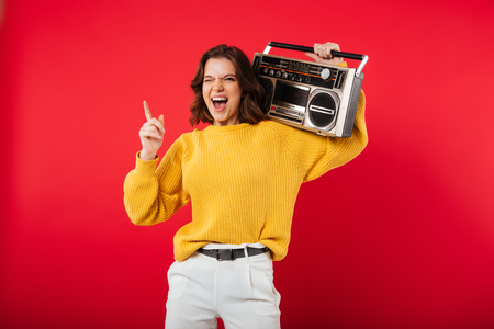 Portrait of a joyful girl with a boombox on her shoulder isolated over pink background