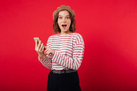 Portrait of an excited woman wearing beret holding mobile phone isolated over pink background