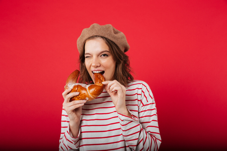 Portrait of a pretty woman wearing beret eating croissant and looking at camera isolated over pink background
