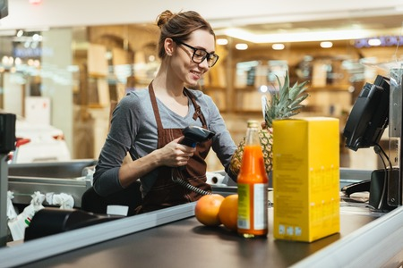 Smiling female cashier scanning grocery items at supermarket Imagens